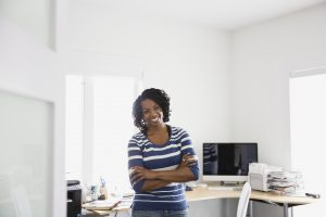 Happy woman standing in home office