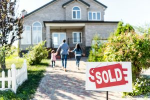 family moving into new house with sold signboard on foreground