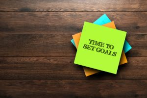 Time To Set Goals, the phrase is written on multi-colored stickers, on a brown wooden background. Business concept, strategy, plan, planning.