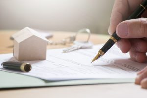 Man hand signing documentation for home mortgage with a pen. Keys and home icon with empty copy space for Editor's text.