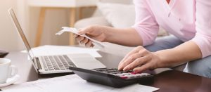 Senior lady calculating bills at home, panorama
