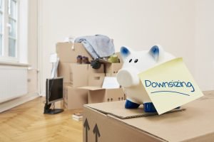 Making the apartment smaller saves money and makes less work. Stacked and packed moving boxes with a piggy bank