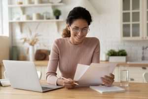 Happy millennial hispanic lady review printed paper documents financial reports